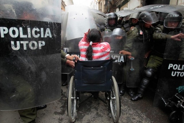 A Bolivian woman taking on a group of riot police